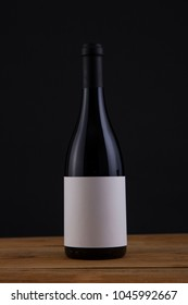 Isolated Red Wine Bottle in a Black Background, fresh and Clean with Black Capsule with White Label