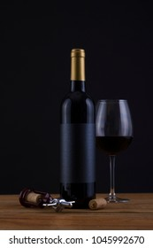 Isolated Red Wine Bottle in a Black Background, fresh and Clean with Gold Capsule with Black Label and Glass