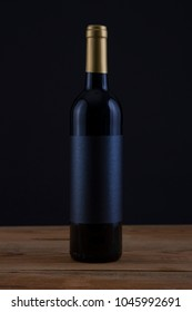 Isolated Red Wine Bottle in a Black Background, fresh and Clean with Gold Capsule with Black Label