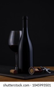 Isolated Red Wine Bottle in a Black and Wood Background, fresh and Clean with Black Capsule with Black Label and Glass