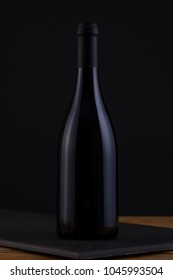 Isolated Red Wine Bottle in a Black and Wood Background, fresh and Clean with Black Capsule