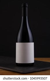 Isolated Red Wine Bottle in a Black and Wood Background, fresh and Clean with Black Capsule with Black White Label