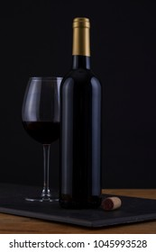 Isolated Red Wine Bottle in a Black and Wood Background, fresh and Clean with Gold Capsule with no Label and Glass