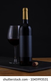 Isolated Red Wine Bottle in a Black and Wood Background, fresh and Clean with Gold Capsule with Black Label and Glass