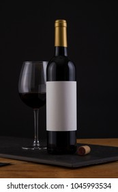 Isolated Red Wine Bottle in a Black and Wood Background, fresh and Clean with Gold Capsule with White Label and Glass