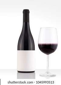 Isolated Red Wine Bottle in a White and Wood Background, fresh and Clean with Black Capsule with White Label and Glass