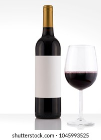 Isolated Red Wine Bottle in a White and Wood Background, fresh and Clean with Gold Capsule with Black Label and Glass