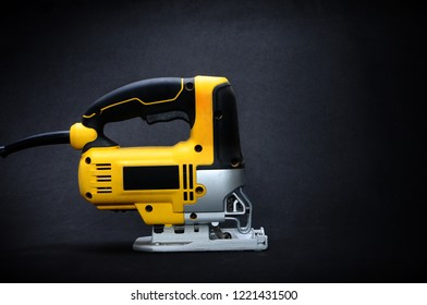 Isolated right side yellow electric jig saw on a dark background