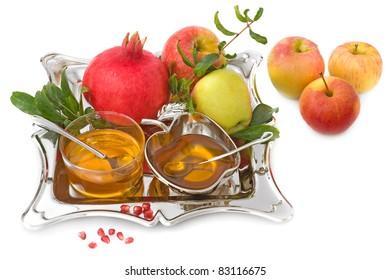 isolated ripe apple  ,pomegranates with leaves and honey for Rosh Hashana– jewish new year