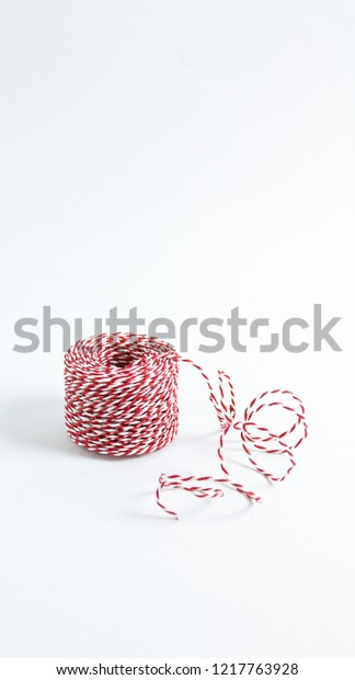 An isolated roll of Christmas string on a white background.