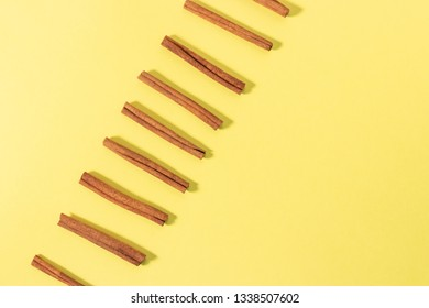 Isolated row of cinnamon sticks from above on a bright yellow background