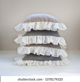 Isolated ruffled throw pillow stack for home decor. Gray and beige pillows with white ruffles.