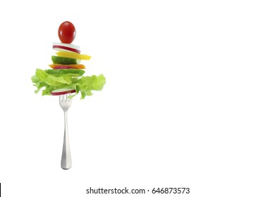 Isolated salad stack with tomato, water chestnut, zucchini, organic vegetable on fork on white background with copy space