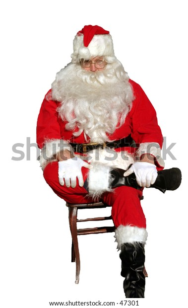 isolated santa sits on a chair with one foot crossed over the other with both hand on his lap