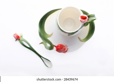 Isolated saucer, cup and spoon decorated with red flower and green color