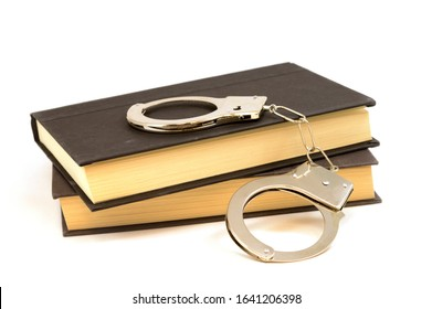 An isolated set of books and handcuffs for the educational study of law and order.