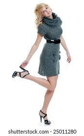 Isolated sexy blond woman wearing a grey knit dress holding shoe