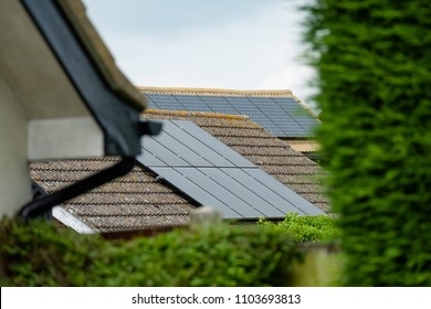 Isolated, shallow focus of newly installed Solar panels on a detached house. Also in view is another house with Solar panels installed to help reduce electric utility bills.