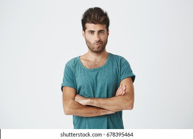 Isolated shot of angry man wearing blue t-shirt with stylish hairstyle holding arms crossed, having skeptical and dissatisfied look. Distrust, skepticism and doubt.