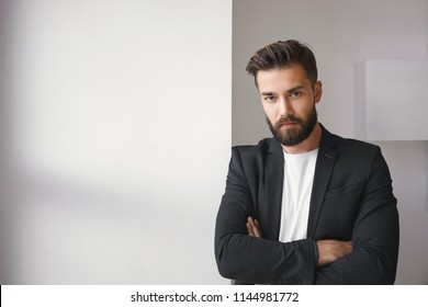 Isolated shot of attractive successful young brunette bearded male entrepreneur wearing trendy jacket over casual white t-shirt keeping his arms folded, expressing reluctancy or disagreement