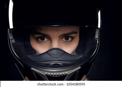 Isolated shot of attractive young brown eyed Caucasian female rider posing in studio wearing safety motorcycle helmet, staring at camera with confident look, ready for contest or competition
