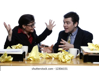 An isolated shot of a businessman and businesswoman discussing ideas at a desk, littered with yellow paper.