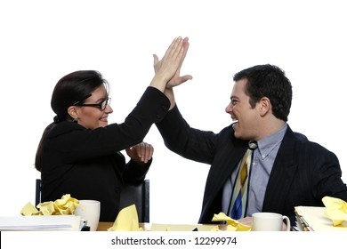 An isolated shot of a businessman and businesswoman giving each other a high five at a desk, littered with yellow paper.