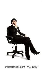 An isolated shot of a businesswoman sitting on a chair and talking on the phone