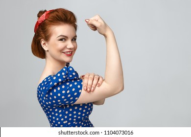 Isolated shot of charming positive young woman in retro clothes smiling broadly, tensing bicep, demonstrating her strong arms. Feminism, girl power, equal women's rights and independence concept
