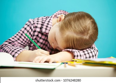 Isolated shot of child with poor posture sitting at desk and do homework. Girl rested her head on table and writes in notebook.