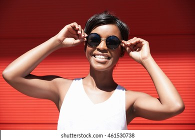 Isolated shot of cute dark-skinned female model making faces while putting on her round hipster sunglasses, smiling, looking funny, happy, joyful and carefree. Human face expressions and emotions