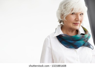 Isolated shot of elegant fasionable white haired elderly businesswoman wearing stylish silk scarf and white formal shirt having confident look, posing against blank copyspace wall background