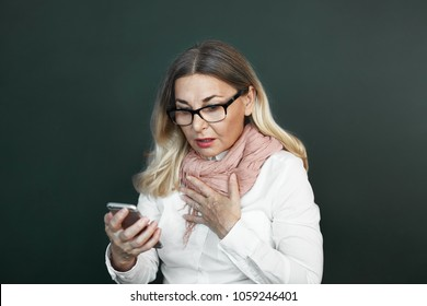 Isolated shot of fashionable senior woman with blonde hair holding hand on her chest and opening mouth in shock, stunned with bad negative news that she reads via text message on smart phone