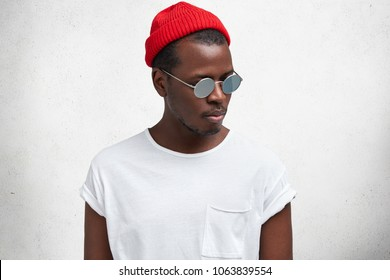 Isolated shot of fashionable serious young African American male in sunglasses, red trendy hat and casual t shirt, looks aside, isolated over white studio background. People and style concept