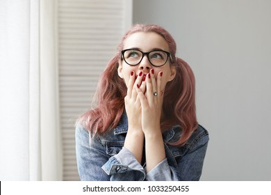 Isolated shot of fashionable young European woman with pink colored ponytails and red nails covering mouth with both hands and looking up with excited expression, overjoyed with great positive news