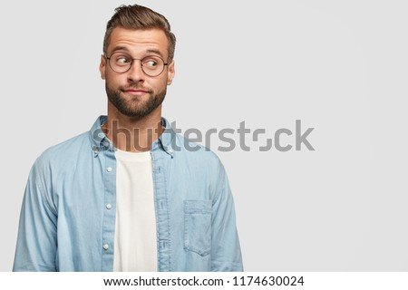 0c8715eaa4b Isolated shot of funny bearded man designer or freelancer looks  thoughtfully aside