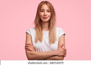 Isolated shot of good looking female student dressed casually, spends weekend at home, listens attentively mother`s instructions, going to have walk with boyfriend or friends, has attractive look