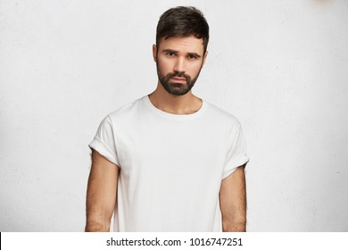 Isolated shot of handsome man with dark thick stubble, wears casual white t shirt, poses against concrete wall. Serious attractive man ponders about something while spends free time at home alone