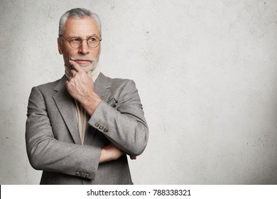Isolated shot of handsome thoughtful businessman dressed in formal suit, looks thoughtfully aside, keeps hand under chin, tries to generate new ideas for startup, isolated on white wall, copy space