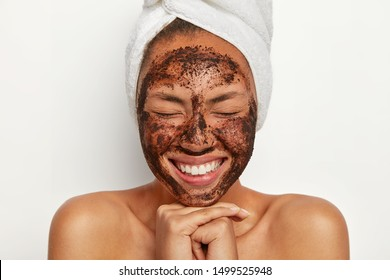 Isolated shot of happy Afro American lady keeps hands together under chin, eyes shut, shows white perfect teeth, cleans face with coffee scrub, enjoys facial treatment, keeps eyes shut. Spa procedure