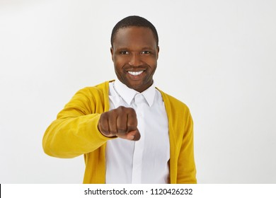 Isolated shot of happy positive young Afro American man wearing stylish clothes posing in studio, smiling broadly and holding clenched fist in front of him, ready to bump knuckles while greeting you