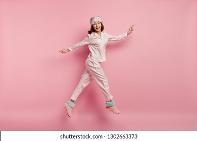 Isolated shot of joyful young woman with happy expression, jumps in air, dressed in pyjamas and domestic slippers, spreads hands, poses over pink background, smiles broadly. Good morning concept