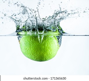 Isolated shot of a lime splashing down through water on a white background