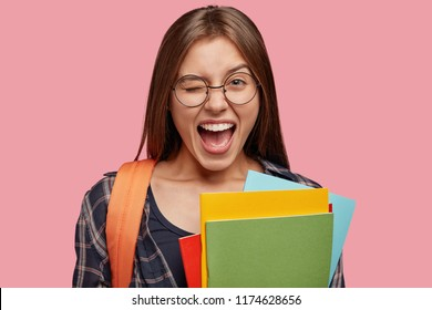 Isolated shot of optimistic Caucasain girl blinks eyes, opens mouth widely, has fun together with groupmates, likes reading and learning something new, ready for strating new year of studying