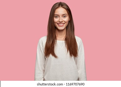 Isolated shot of pleasant looking cheerful brunette youngster has appealing look, healthy skin, dressed in casual white sweatshirt, poses against pink studio wall. Happiness and lifestyle concept