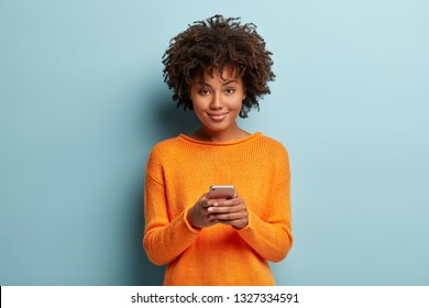 Isolated shot of positive smiling woman holds modern cellular, enjoys wireless internet, checks bank account or sends message in social networks, wears orange clothes, models over blue background