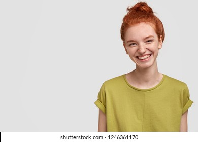 Isolated shot of pretty adult with foxy hair, broad smile, wears casual outfit, being entertained by friend during party, tilts head and looks with joy, dressed casually, models over white wall