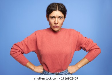 Isolated shot of serious displeased young woman in pinkish sweater frowning, holding hands on her waist, being stubborn, expressing disagreement. Human facial expressions and body language