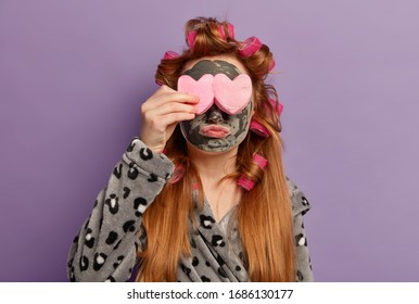 Isolated shot of small female child covers eyes with cosmetic sponges, applies beauty clay mask, makes curly hairstyle, pouts lips, dressed in domestic bathrobe, poses against purple background