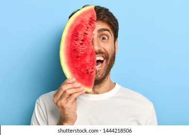 Isolated shot of smiling young male has natural summer snack, holds slice of fresh watermelon near face, has perfect mood, wears white t shirt, isolated on blue. Seasonal food, organic nutrition